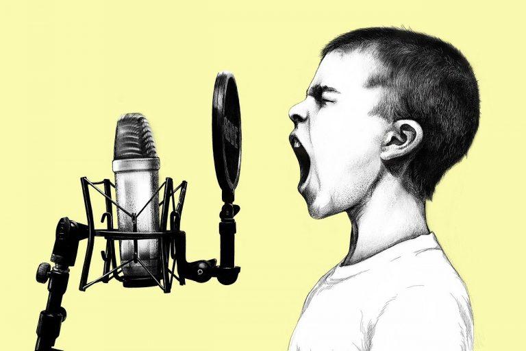 少年がマイクで歌う